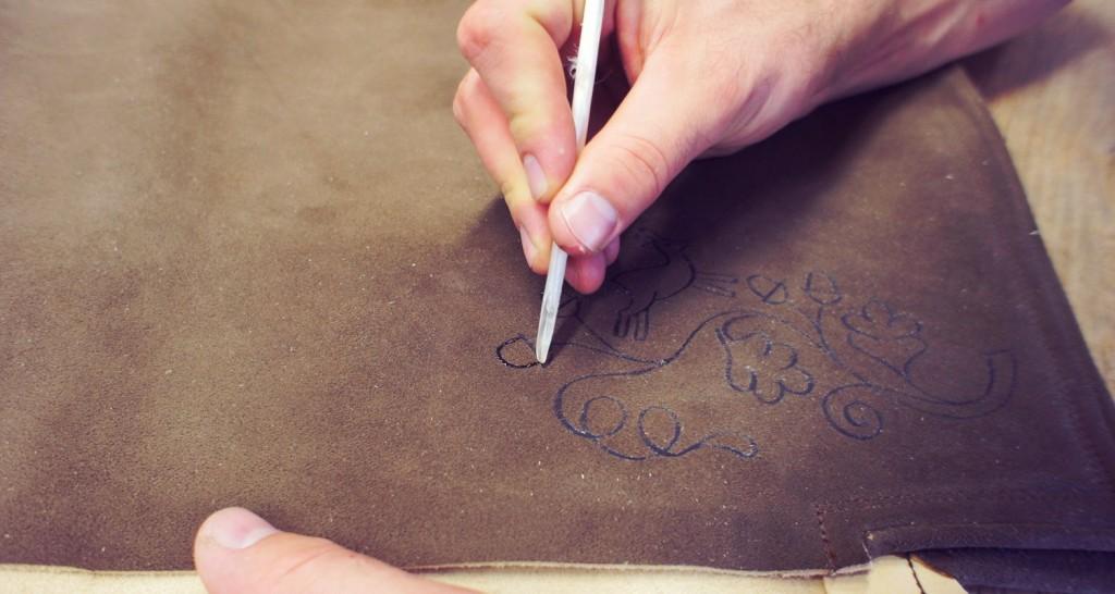3. Schritt: Mit einer Entenfeder und Gummi arabicum - dem Pflanzensaft der Akazie - wird das Muster der Stickerei vorgezeichnet.